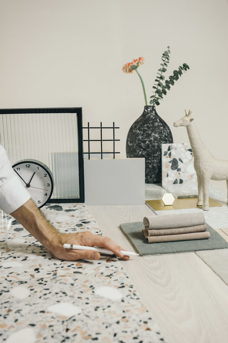 designer standing at workspace with textile and stone samples