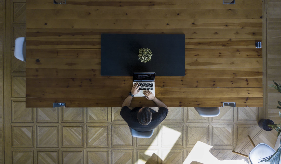bird's-eye view of a man planning a stealth mode startup at a large wooden table