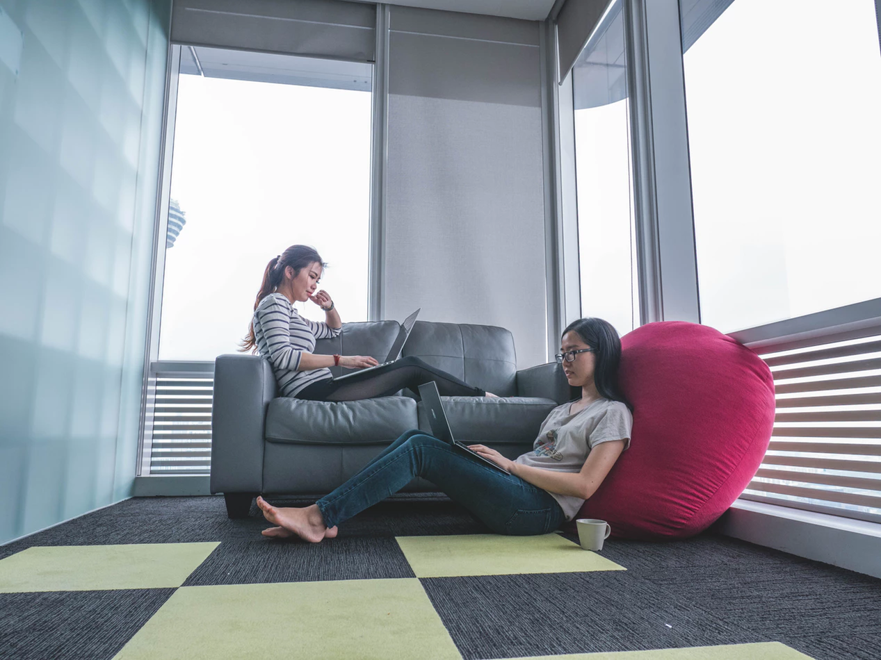 two women working on computers in a coworking space with comfortable furniture