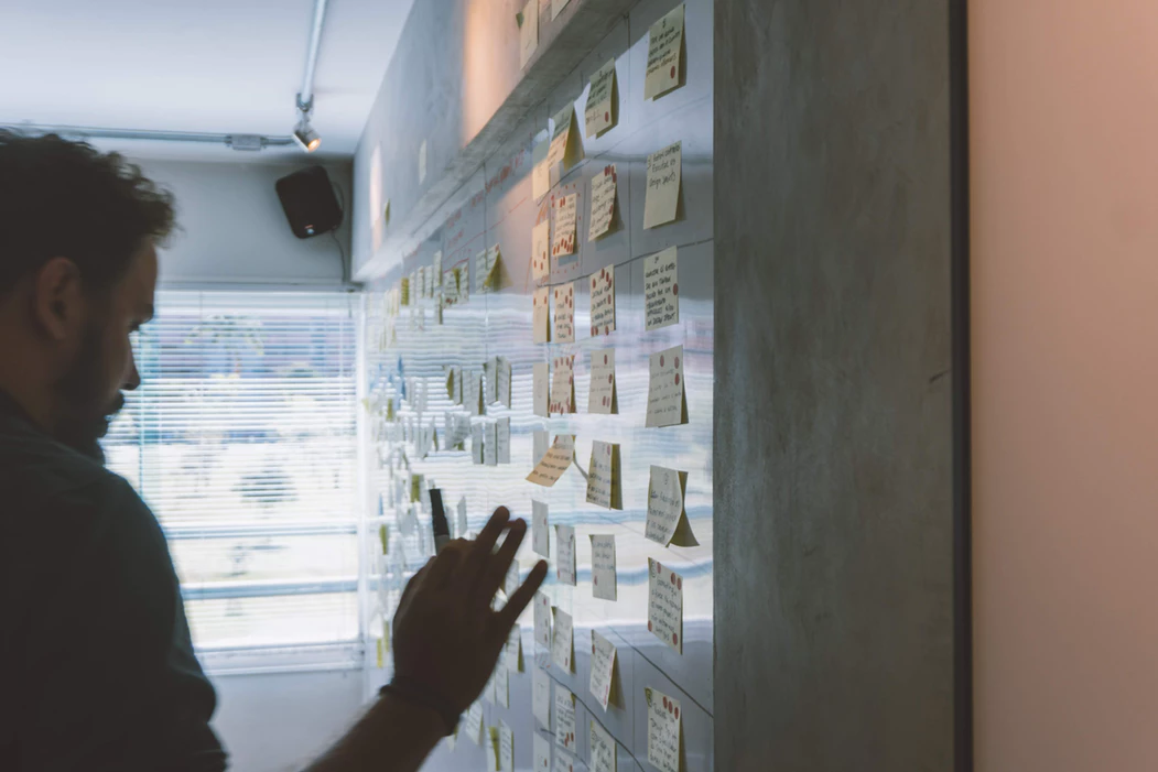 man using sticky notes on a dry erase board to strategize for a stealth mode startup