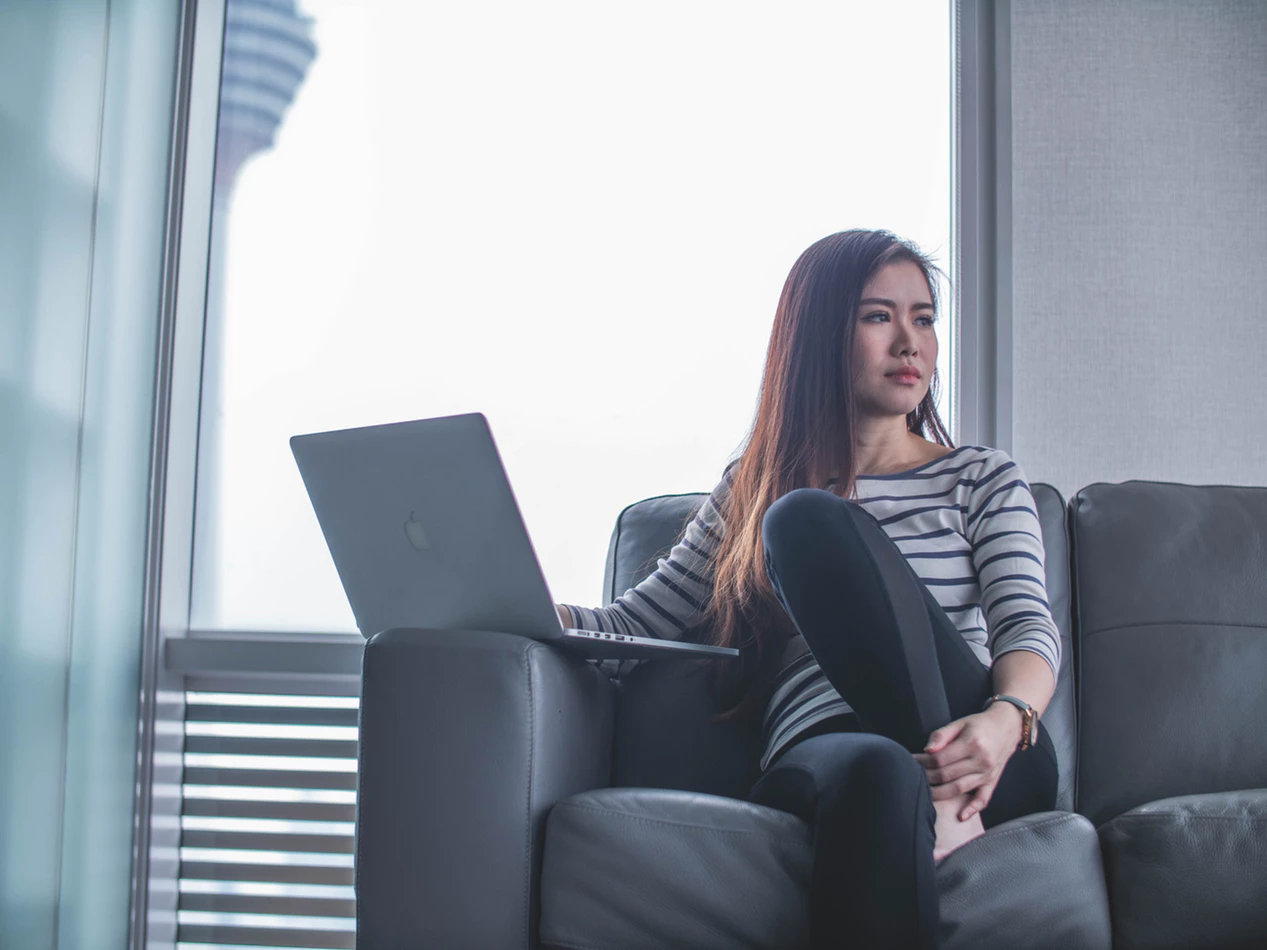 woman looking out an office window while sitting on a sofa and working on her laptop