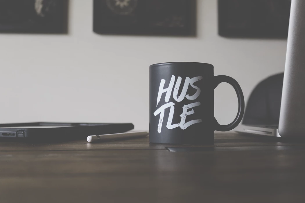 "black ""hustle"" mug on sitting on a wooden office table on a white background"