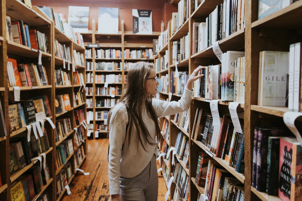woman sifting through shelves of books at a bookstore or library