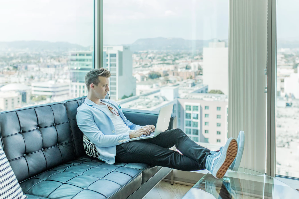 a solopreneur, one of the types of entrepreneurs, working on his laptop in front of a window with his feet propped up on a table