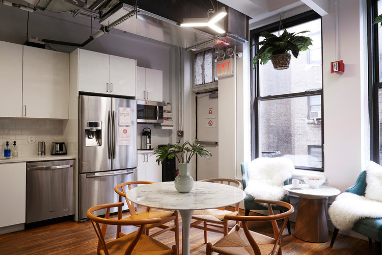 kitchen area with tables and chairs at a coworking space