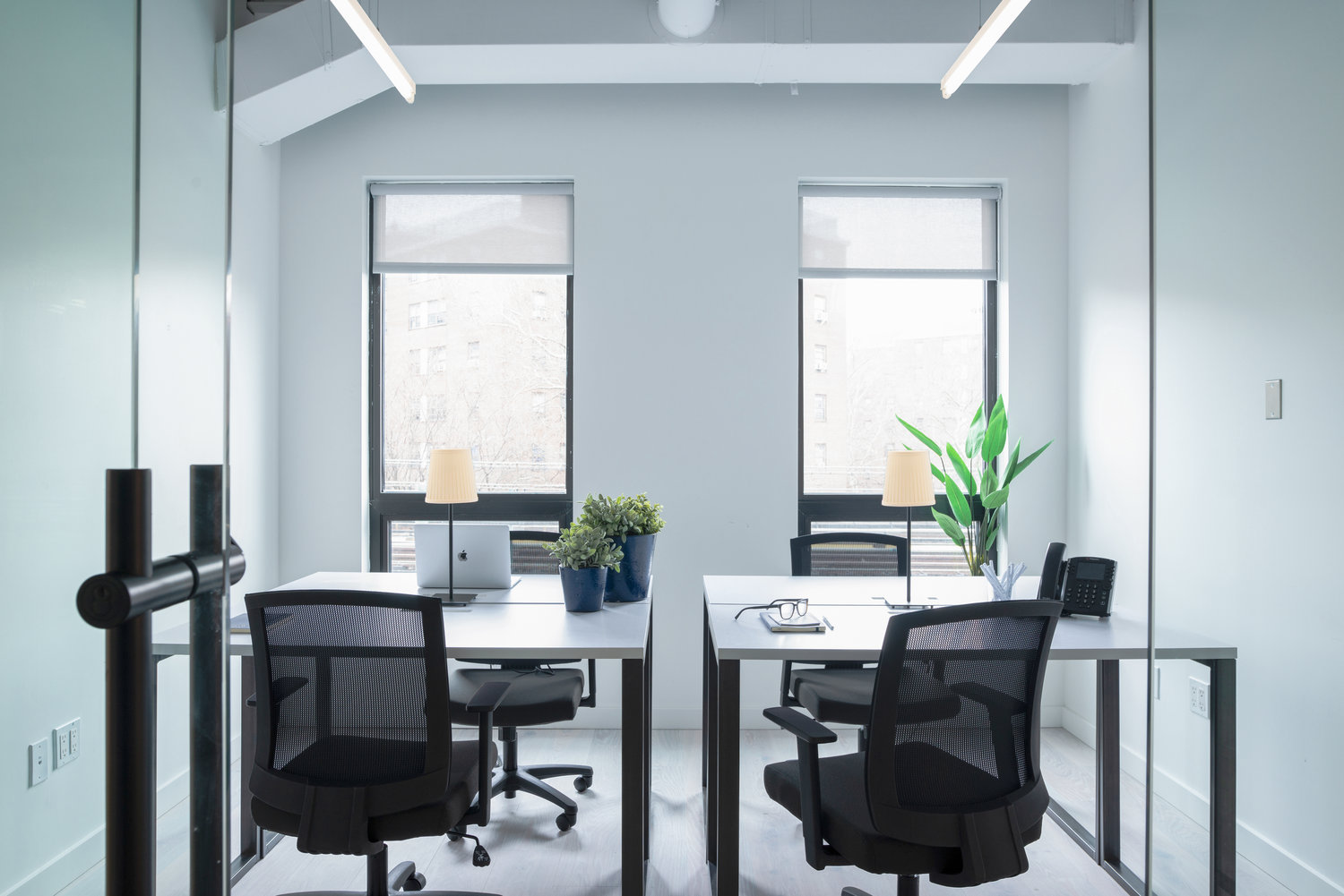 small clean and clutter-free working environment with desks and chairs