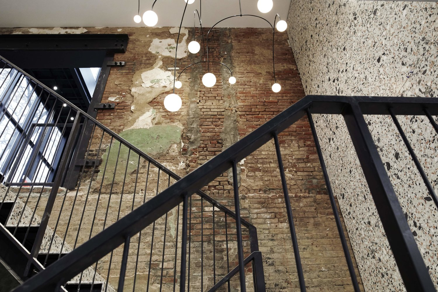 large open staircase with granite and exposed brick