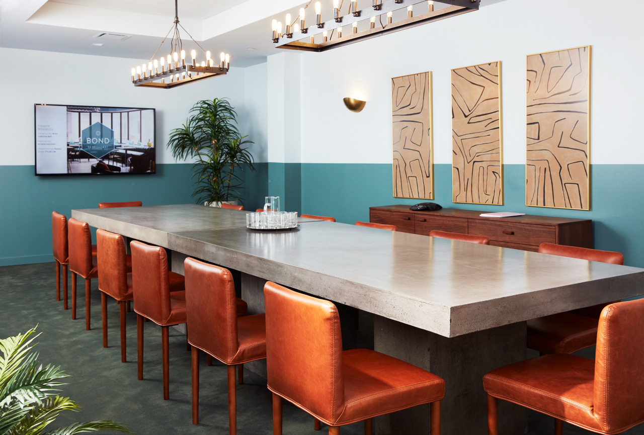 modern office space with large conference table, orange chairs, and plants