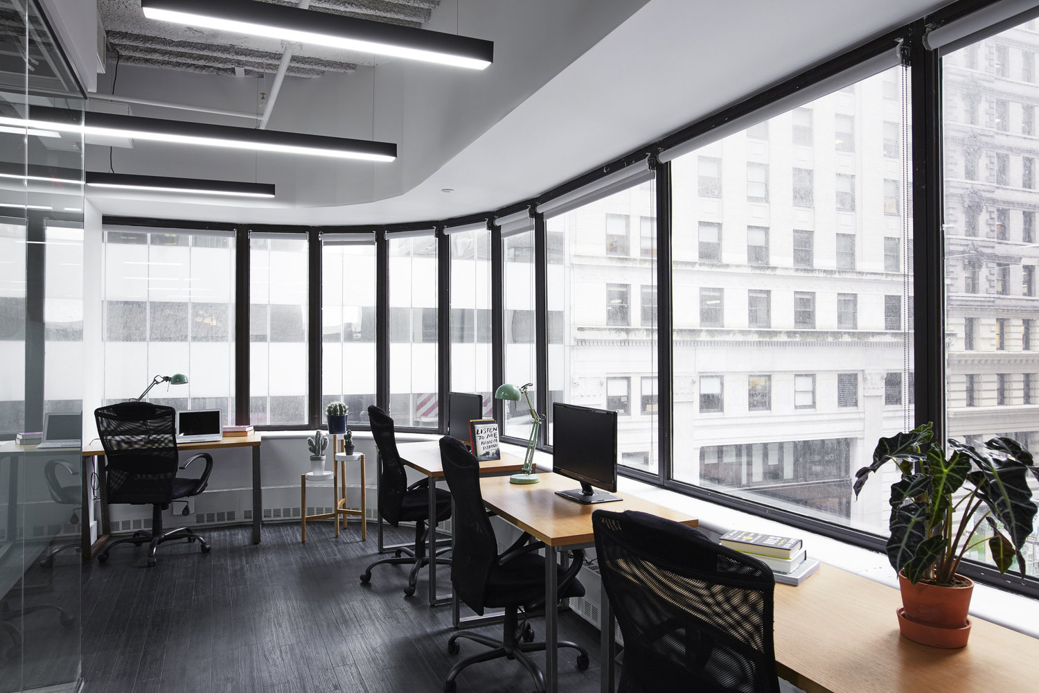 large black and white shared office space with wrap-around windows, desks and chairs