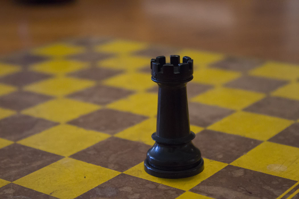 black chess game piece on yellow chess board