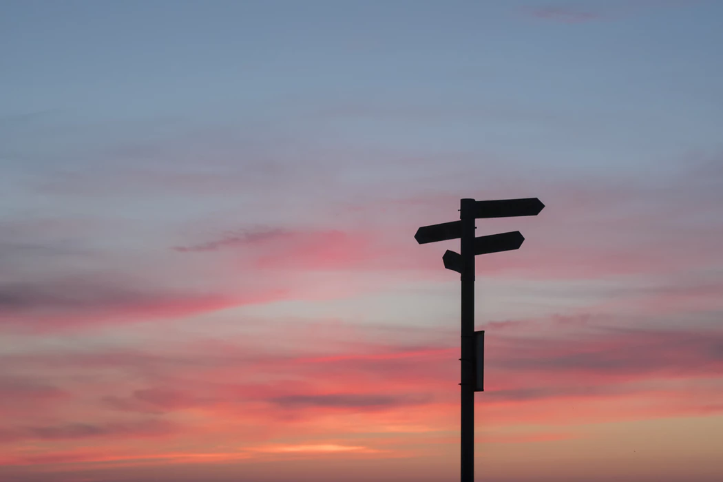 multi-directional signs on a post with sunset sky in the background