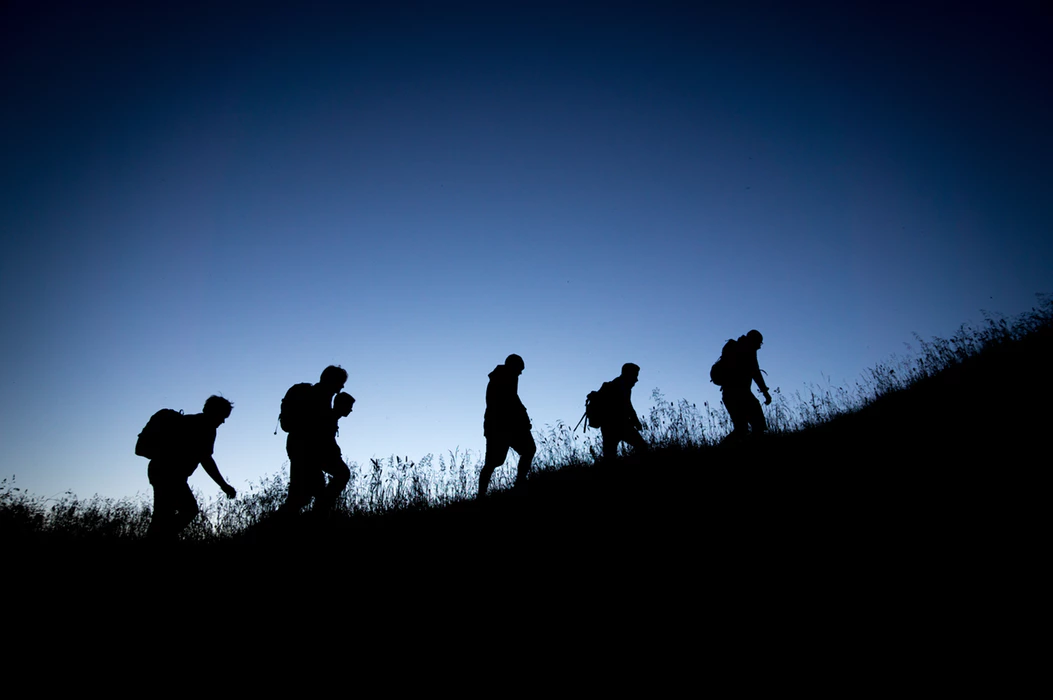silhouettes of hikers climbing a grassy hill
