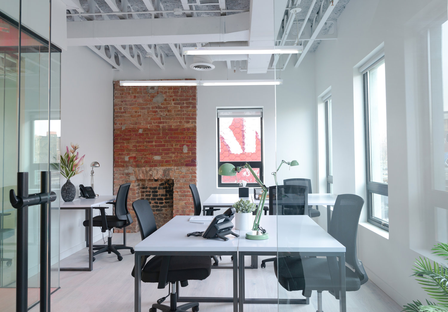 white and brick office area with large tables and chairs