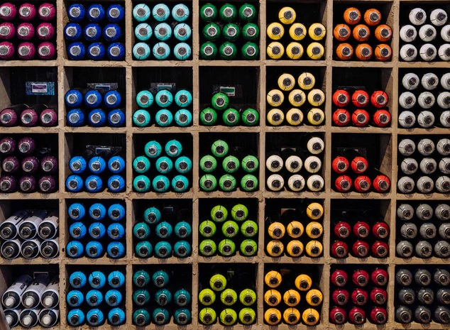 bottles of colored paint organized in cubbies