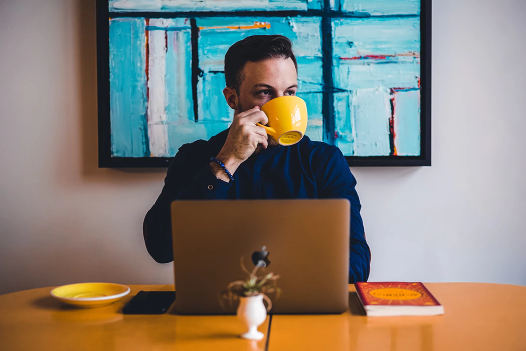 man drinking from a mug while doing remote work with a laptop