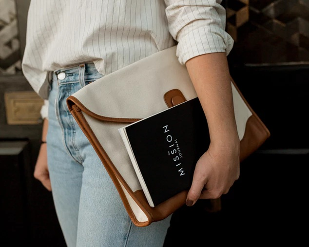 solopreneur carrying a journal and laptop under her arm