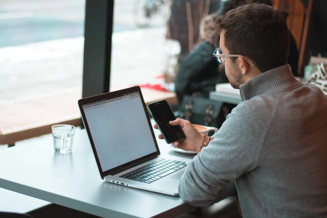 solopreneur using his laptop and mobile phone to work in a cafe