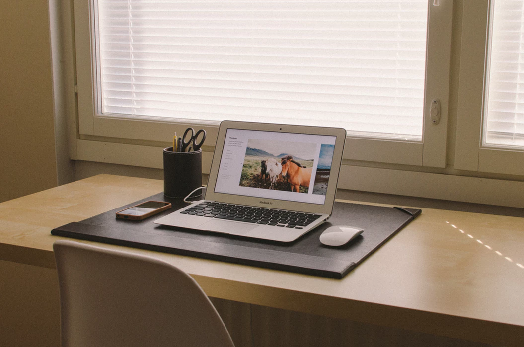 uncluttered desk with laptop, pencil cup, and cell phone