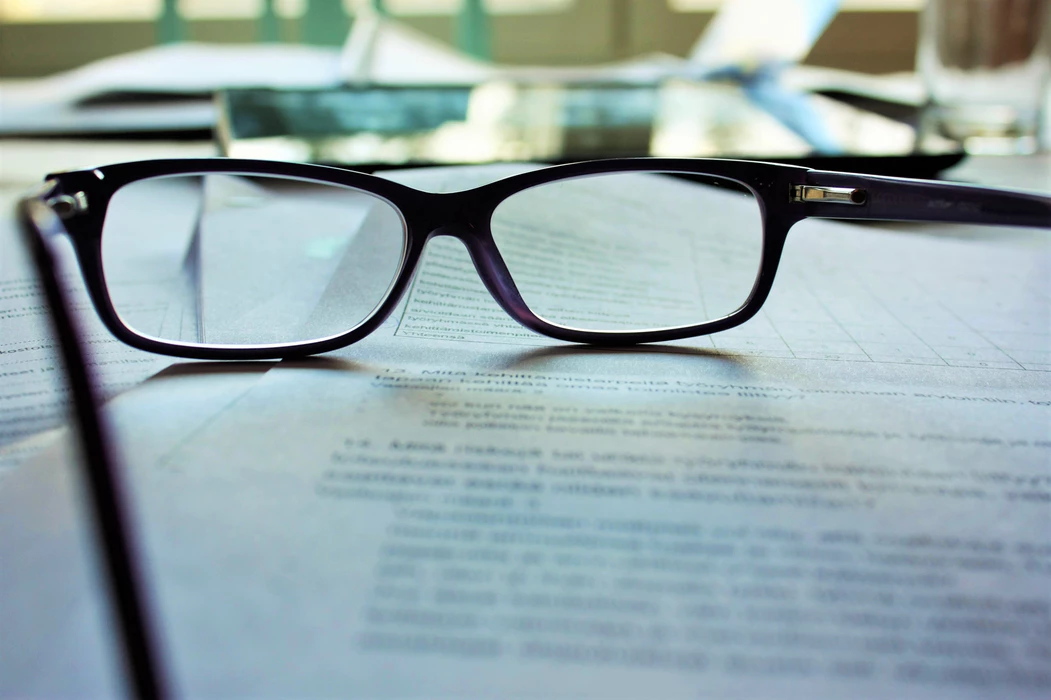 Pair of black glasses on top of stack of papers