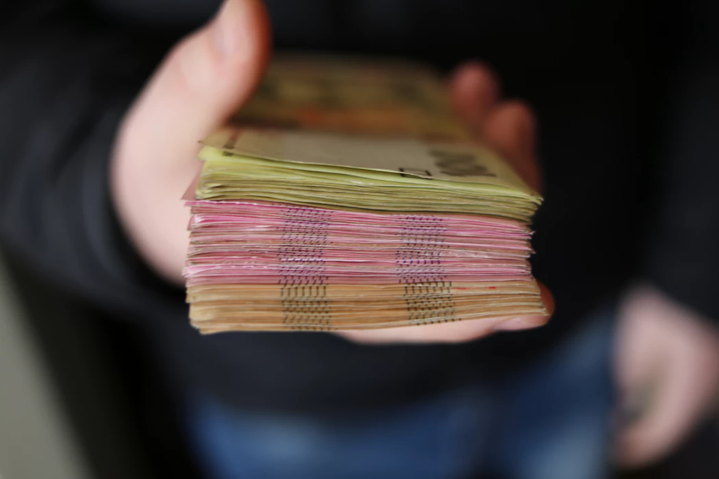 hand holding stack of currency