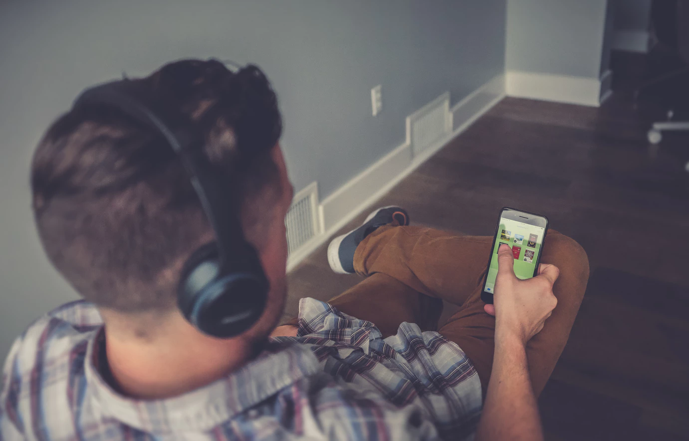digital nomad selecting from the best entrepreneur podcasts on his phone