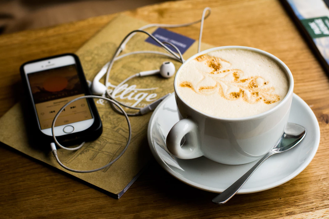 Entrepreneur podcast playing near cup of coffee on wooden table