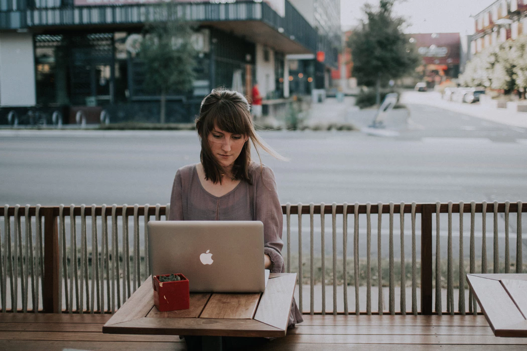 Woman working on a laptop outside in a city