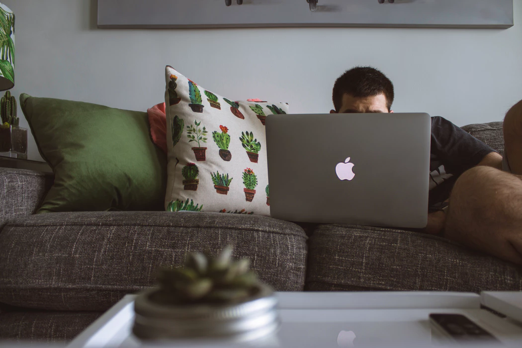 Man enjoying the pros of working from home with his laptop on the sofa