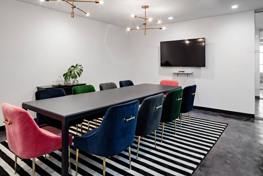 Conference room with long black table and colorful chairs