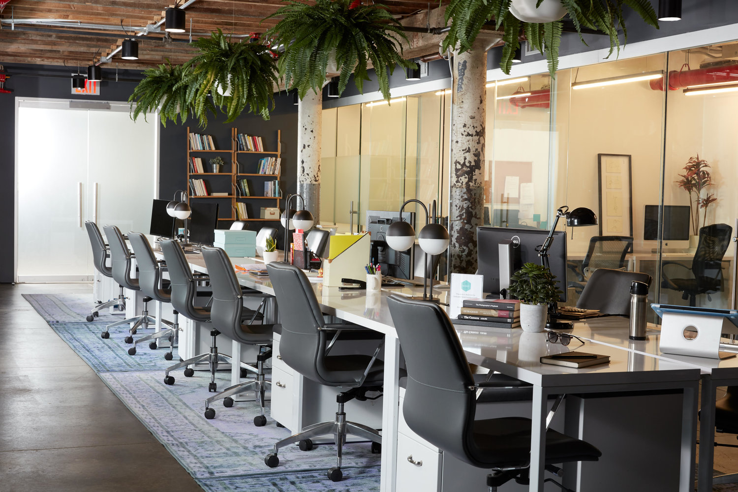 Open office workspace with several black chairs at a long table