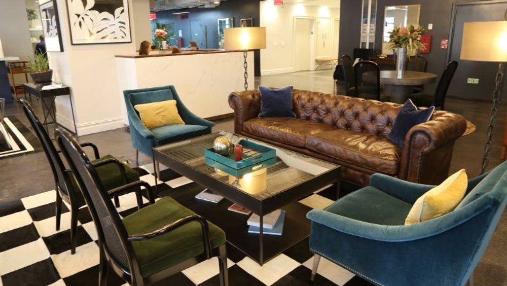 Brown leather sofa and velvet chairs in a coworking space