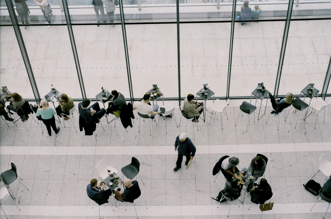 Overhead view of people dining in a large cafe with glass walls