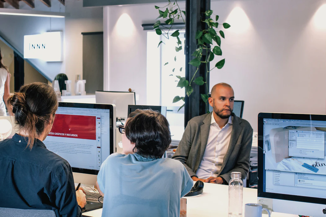 Professionals sitting in front of computers discussing what is a startup