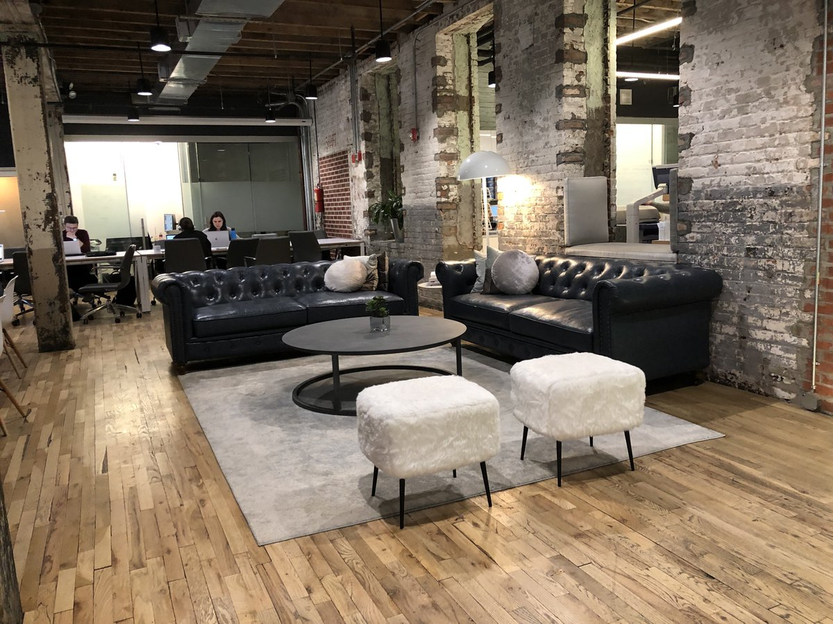 Lounge area with black leather sofas and exposed brick walls