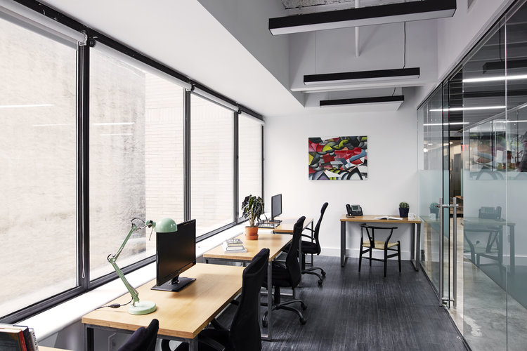 Coworking space with wooden desks facing windows