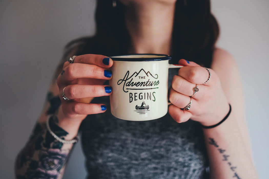 "Woman holding coffee mug that says ""The adventure begins"""