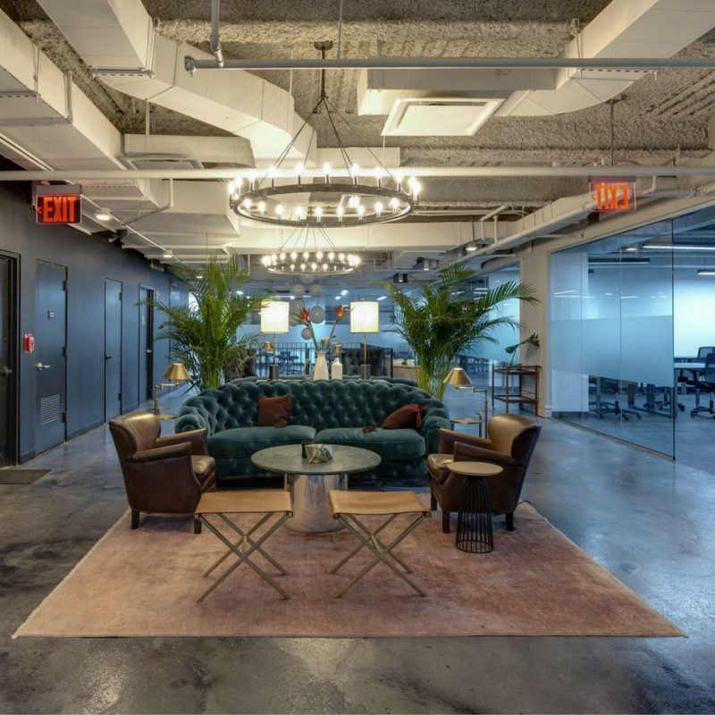 nicely furnished startup office space with comfy couch and large chandelier