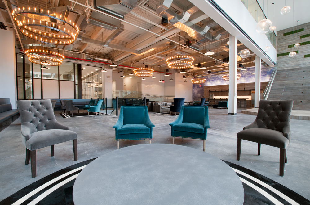 beautiful startup office space with large chandeliers and colorful chairs
