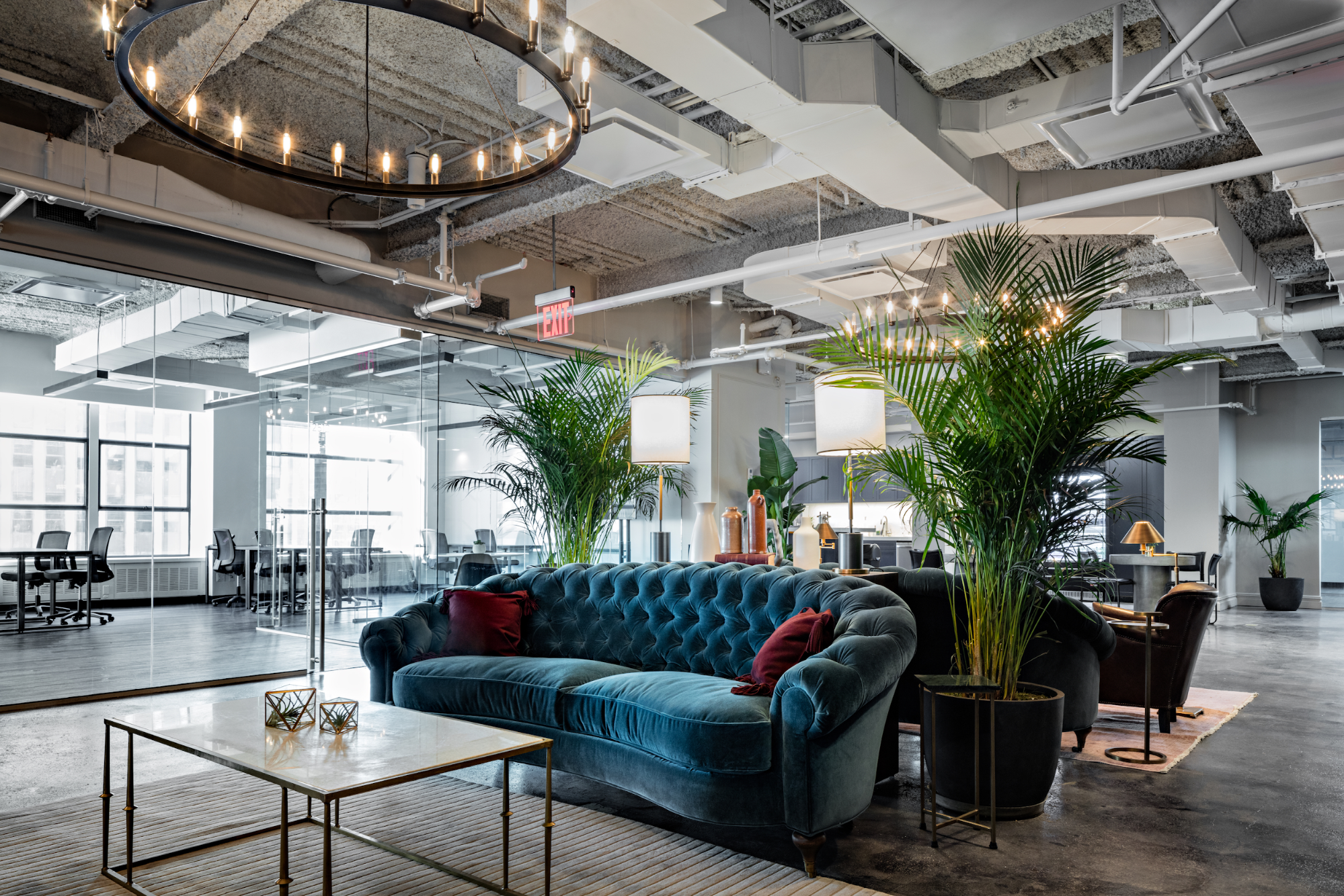 bright open-concept coworking office in a renovated industrial space, with large chandeliers and colorful couches