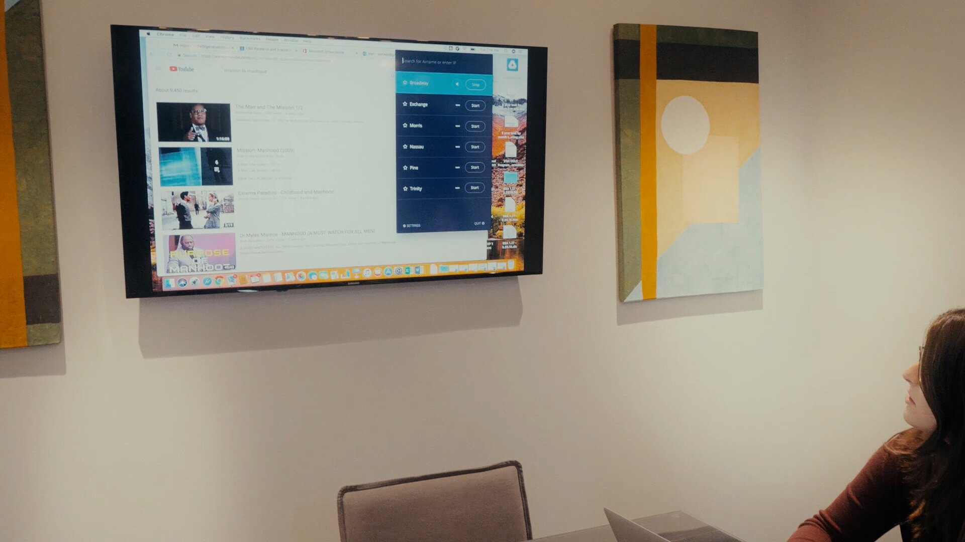 Large computer monitor hanging on the wall of an innovative office