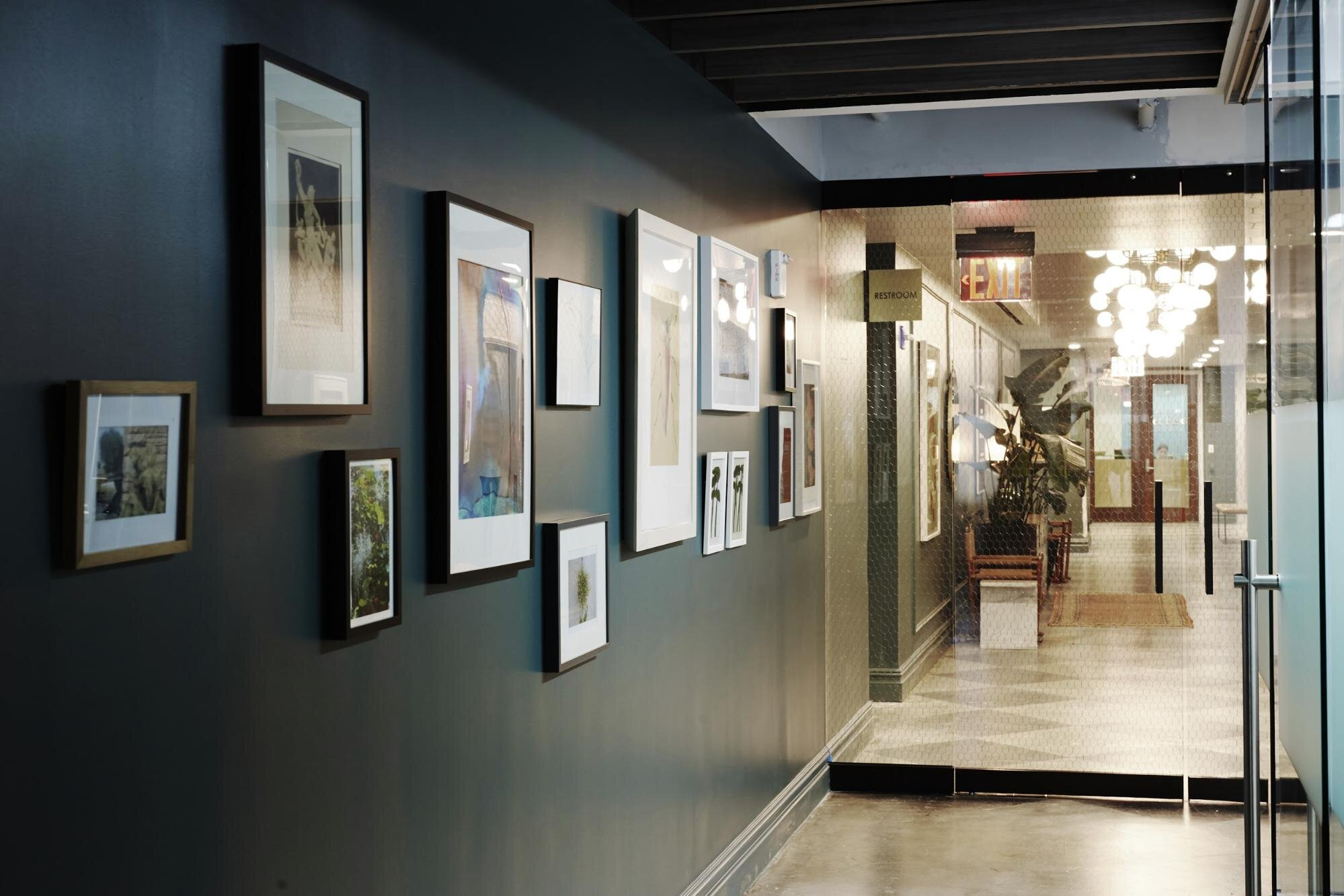 Black wall in an office with picture frames hanging on it