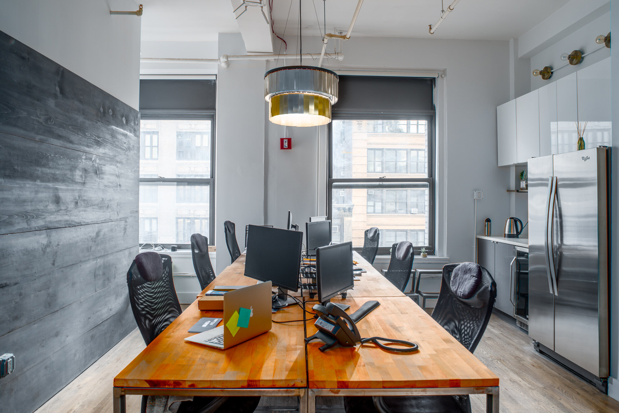 Shared work stations at wooden desks in flexible office space