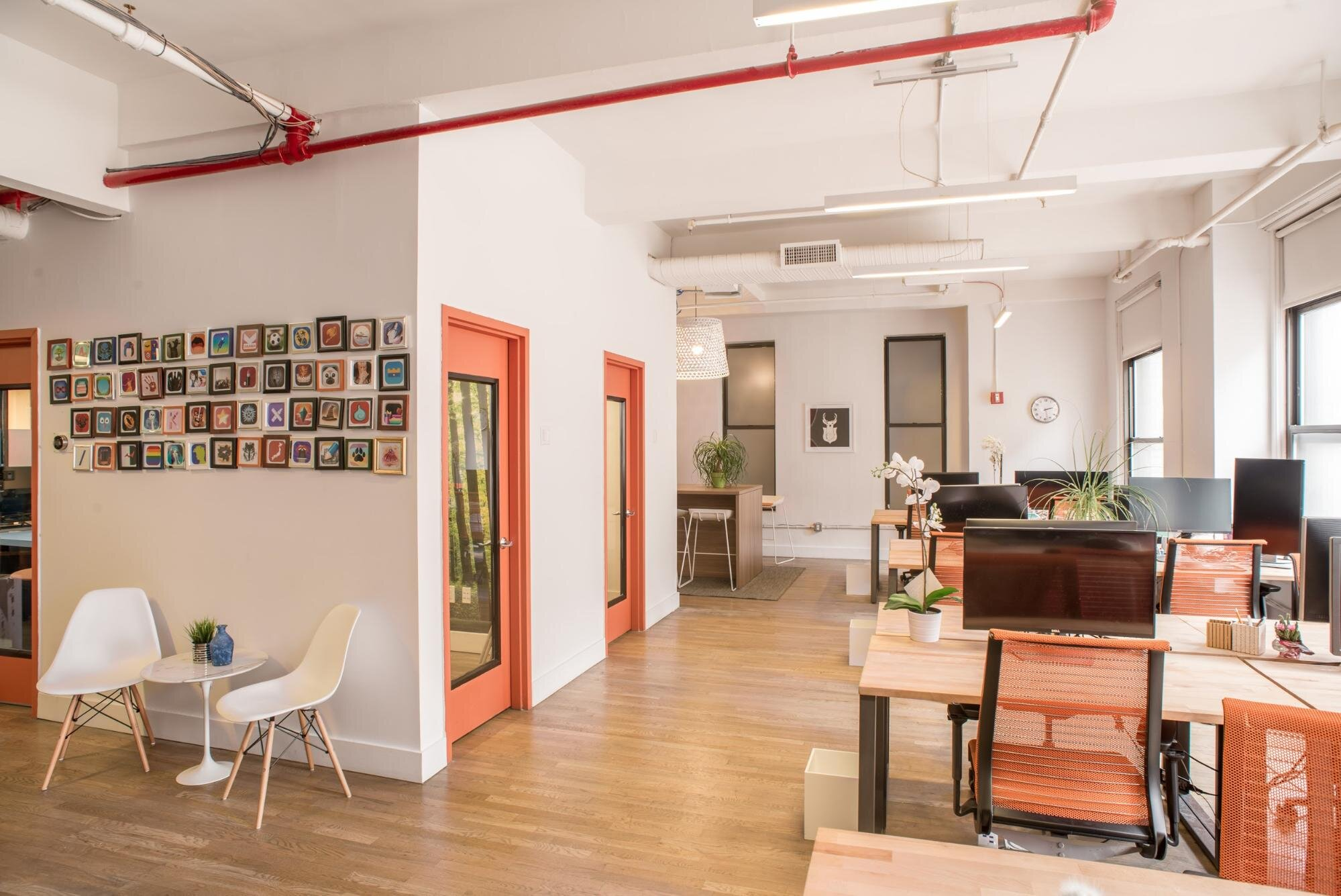 Shared office with several desks, white walls, and red doors