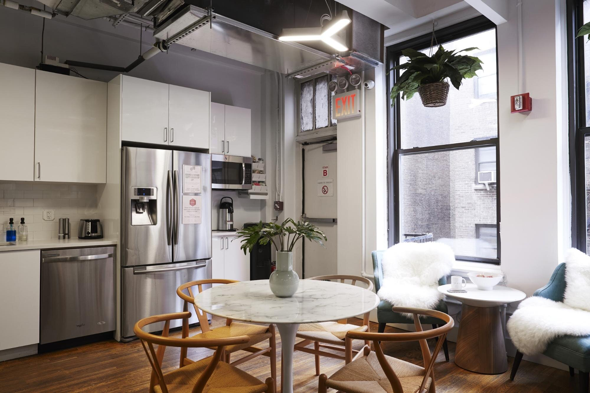 Office kitchen with white cabinets, large window, round table, and chairs