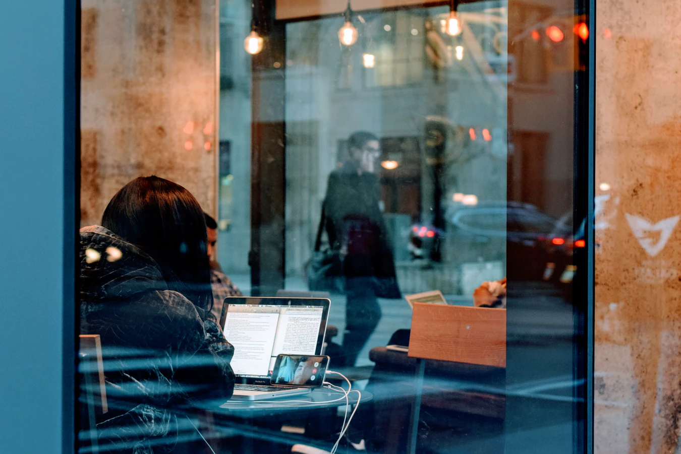 Woman in window of a coffee shop whose following virtual meeting etiquette
