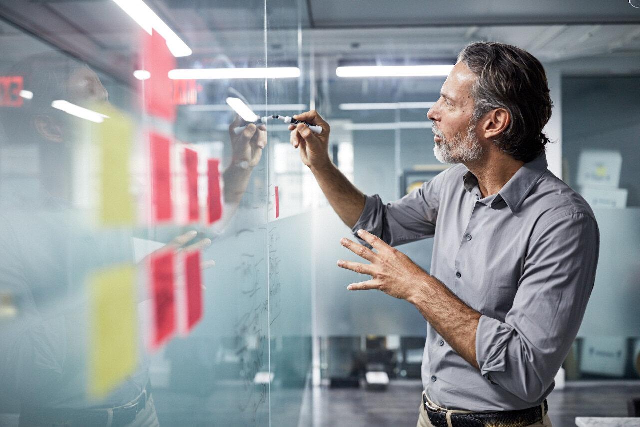 Employee in a futuristic office working on a digital workboards