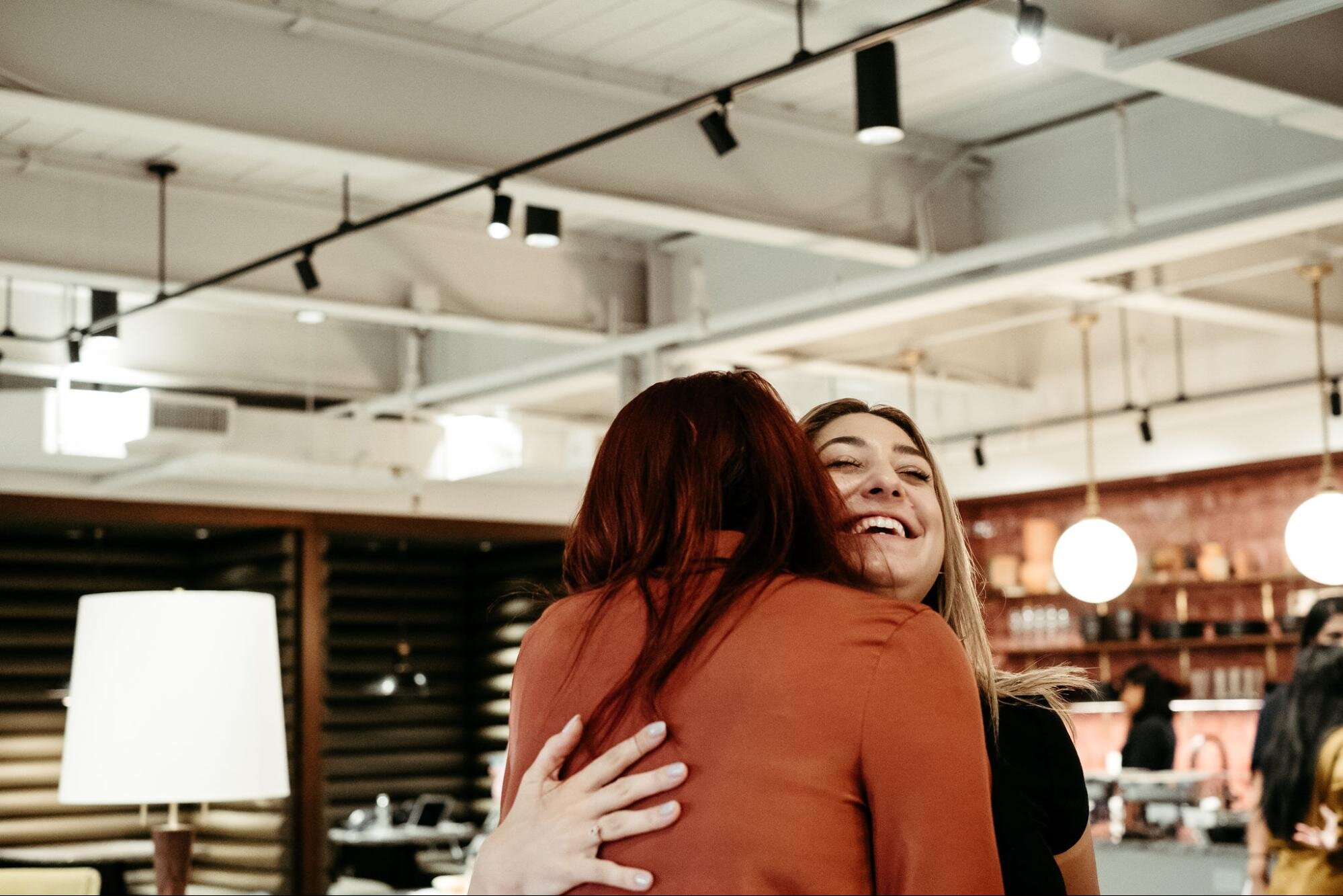 two employees hugging that resolved conflict in the workplace