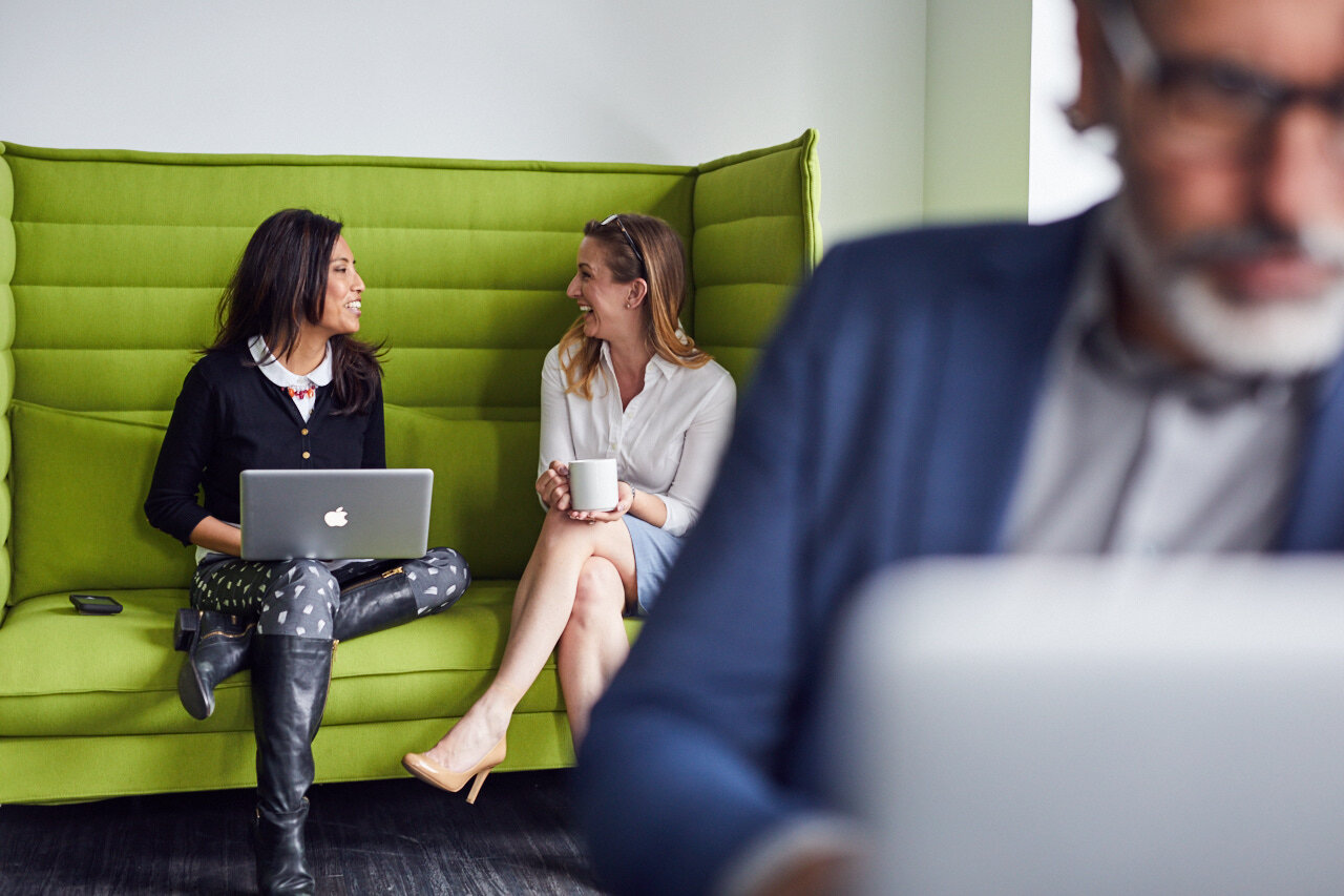 Two employees on a couch discussing workplace inclusion