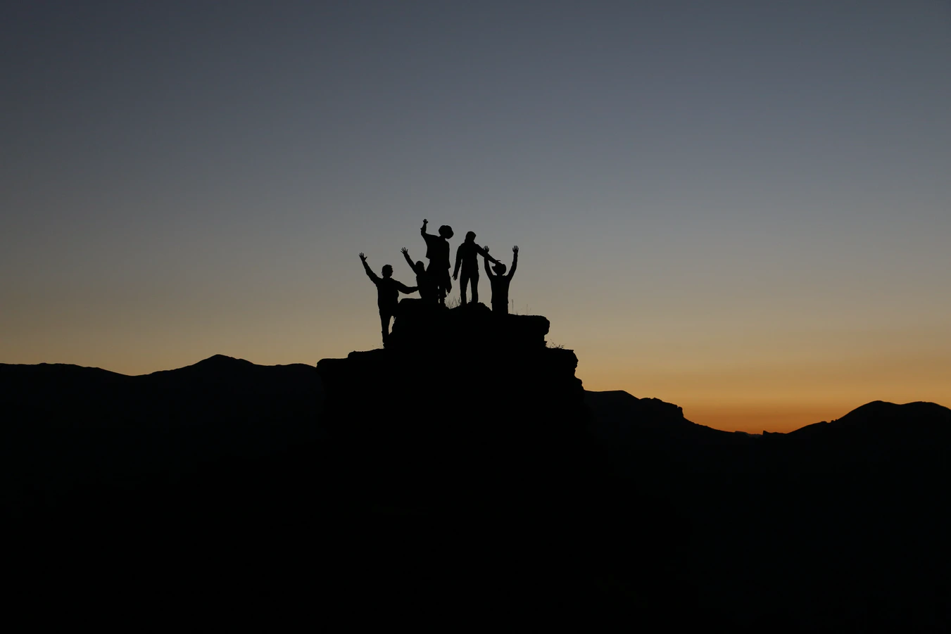 Silhouette of people hiking at sunset