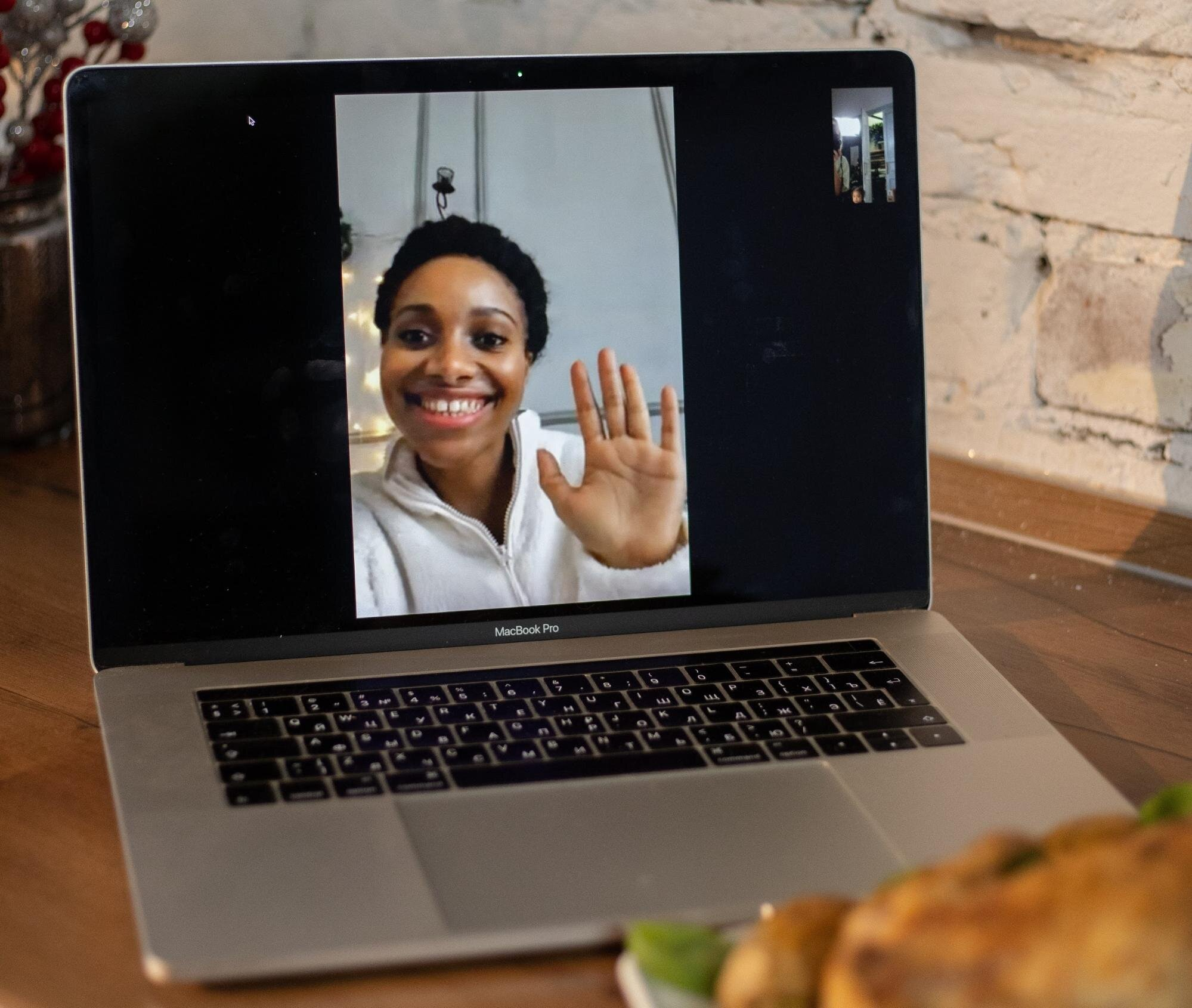 Employee waving at other employees during a virtual retreat
